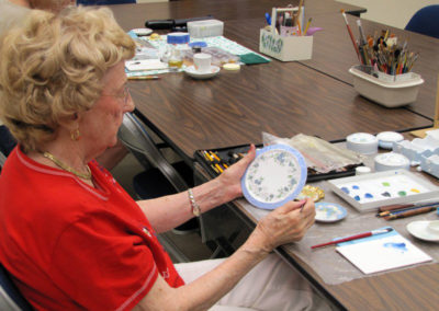 lady examining her painted dish